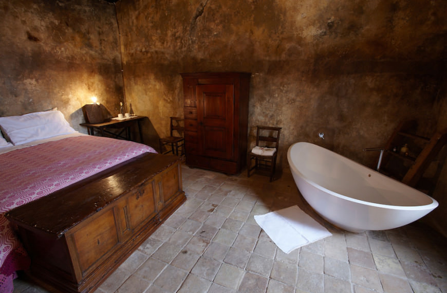A double room in the Albergo Diffuso Sextantio in Santo Stefano di Sessanio, Abruzzo, Italy. As the original buildings had no functioning bathrooms, modern furnishings like this bath tub have been placed in a way as to reduce their impact on the space as much as possible to retain the original feel.